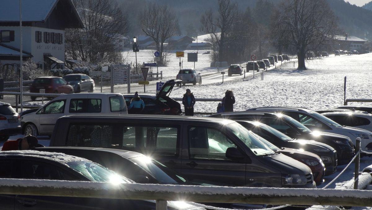 Belebte Straße und gut gefüllter Parkplatz in Oberbayern