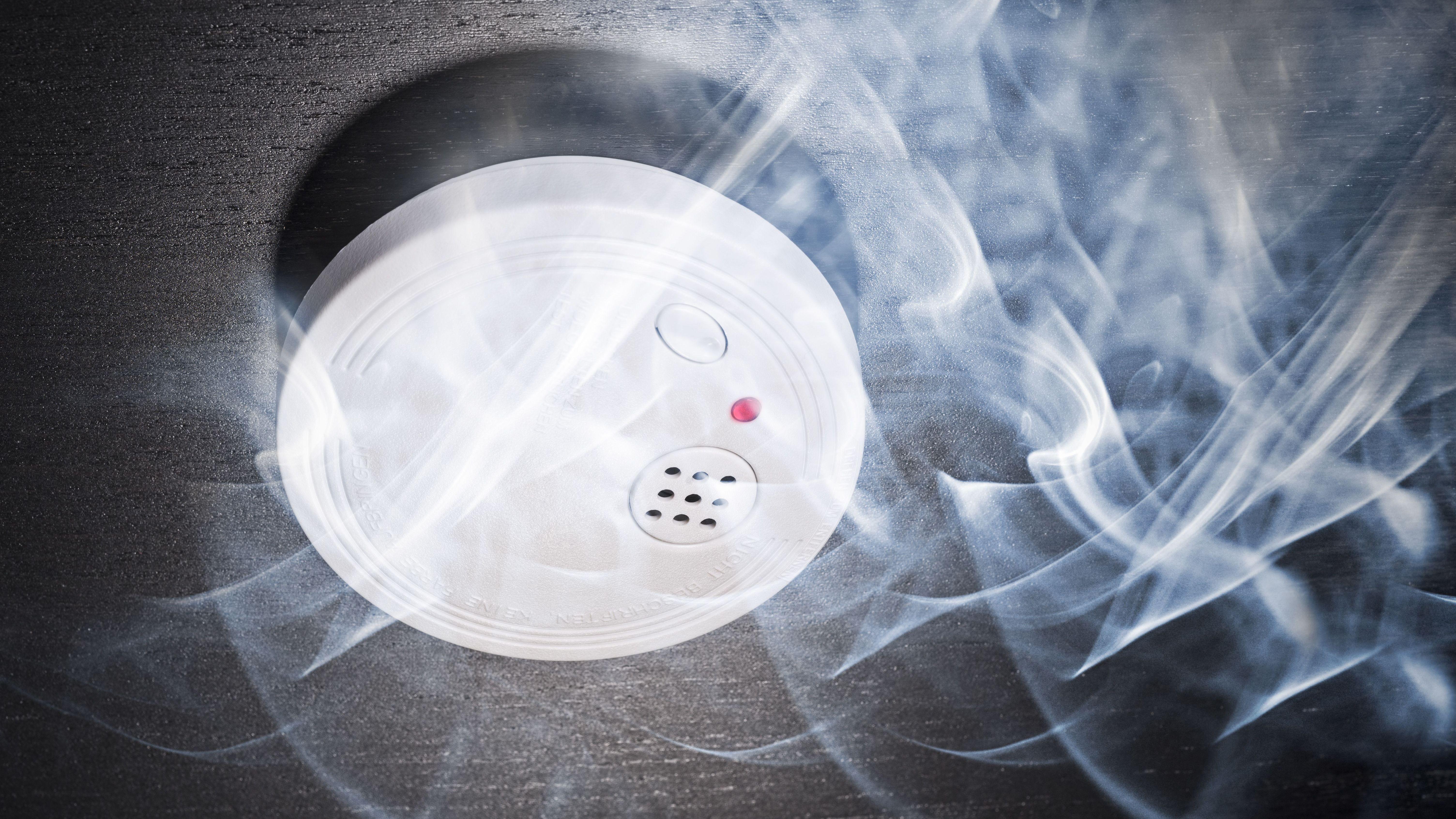 Rauchmelder auf dunkler Wand im Rauch eines Brandes