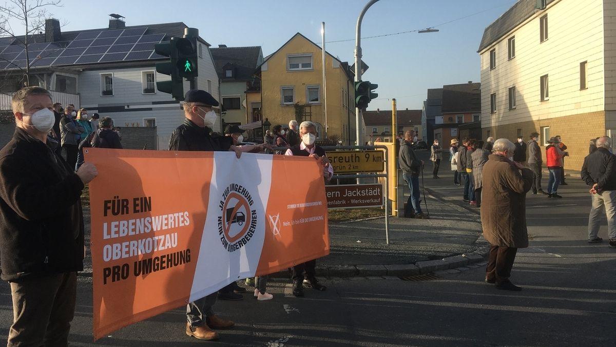 Bürger demonstrieren für den Bau einer Umgehungsstraße und halten ein Transparent in den Händen, auf dem steht: Für ein lebenswertes Oberkotzau, pro Umgehung.