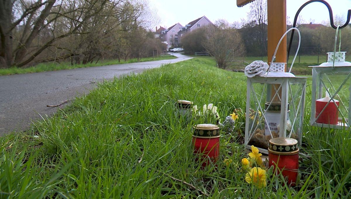 Ein Holzkreuz und Grablichter an einem Radweg in Bayreuth.