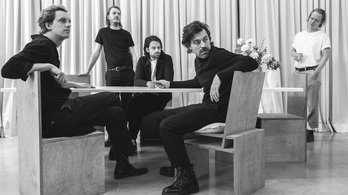 Drei Männer sitzen um einen runden Tisch, zwei weitere stehen links und rechts dahinter - Das Popquintett Balthazar