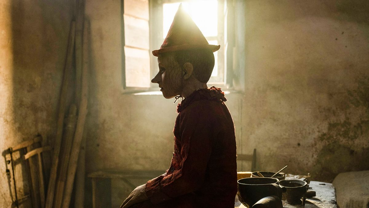 """Ein Junge mit Hut sitzt im Gegenlicht vor einem Fenster in einem ärmlichen Raum: Szene aus """"Pinocchio"""""""