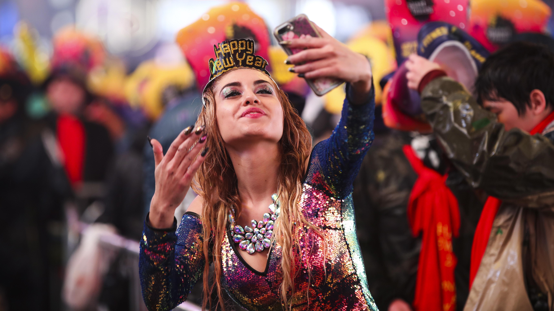 """Eine Frau, glitzerndes Oberteil, auffällig geschminkt, trägt eine Krone mit der Aufschrift """"Happy New Year"""" und macht ein Selfie von sich in einer feiernden Menschenmenge auf dem Times Square in New York."""
