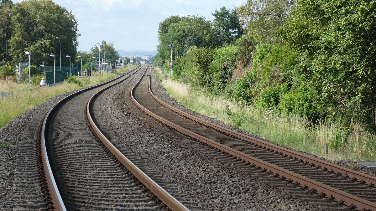 Leere Bahngleise in einer grünen Landschaft