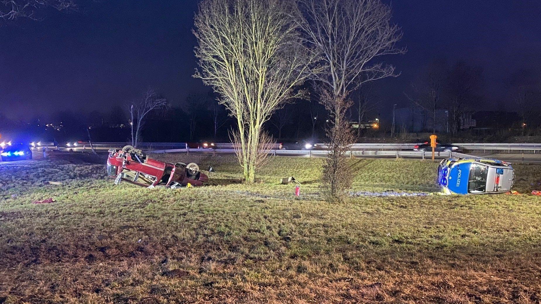 Links das Fluchtauto auf dem Dach liegend, rechts das umgekippte Polizeiauto