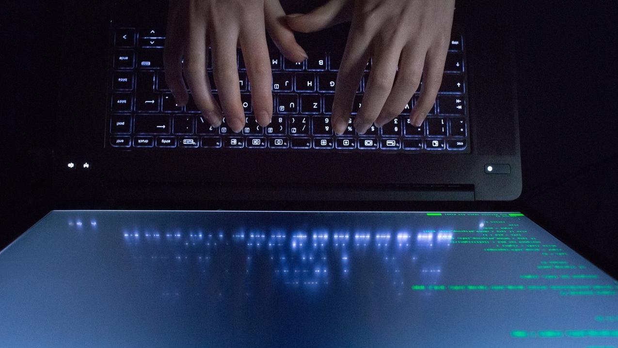 Hände tippen auf einem Laptop, am Bildschirm ein Programmcode.