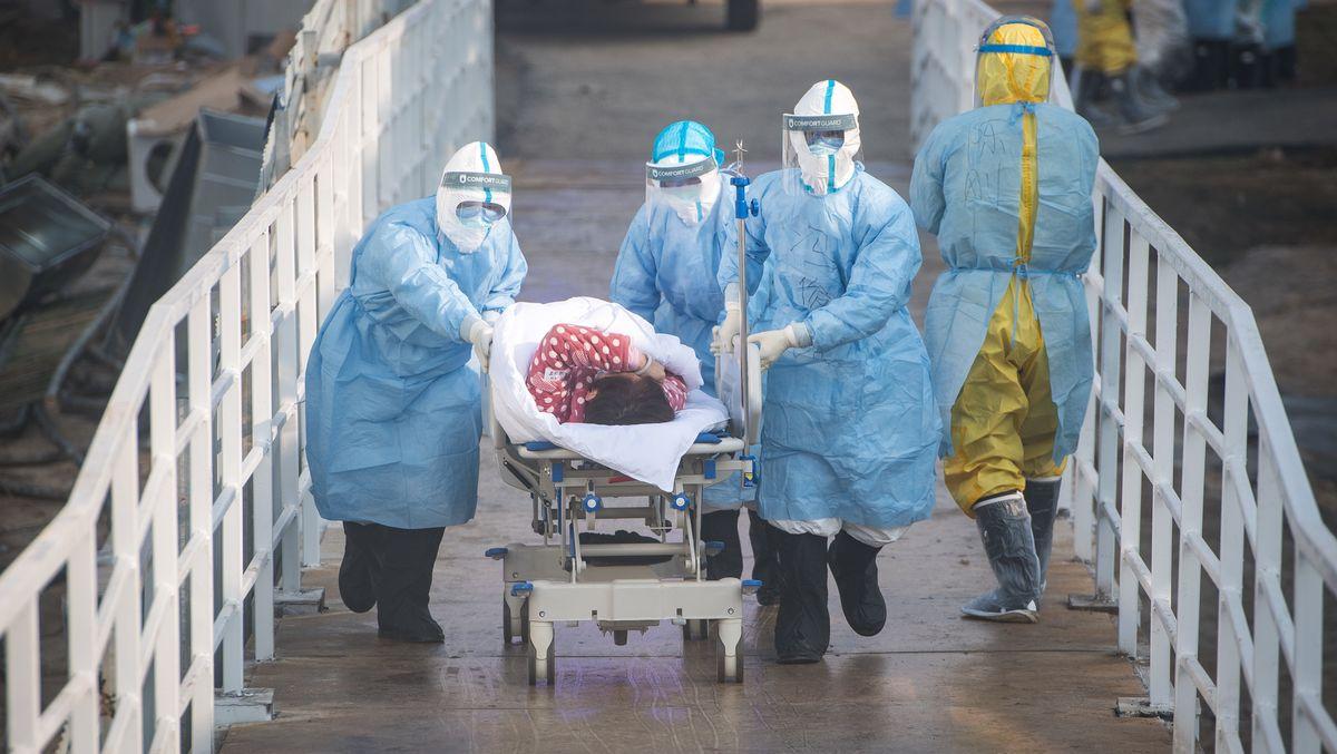 Klinikmitarbeiter im Huoshenshan Hospital in Wuhan bringen einen Corona-Patienten auf Station.