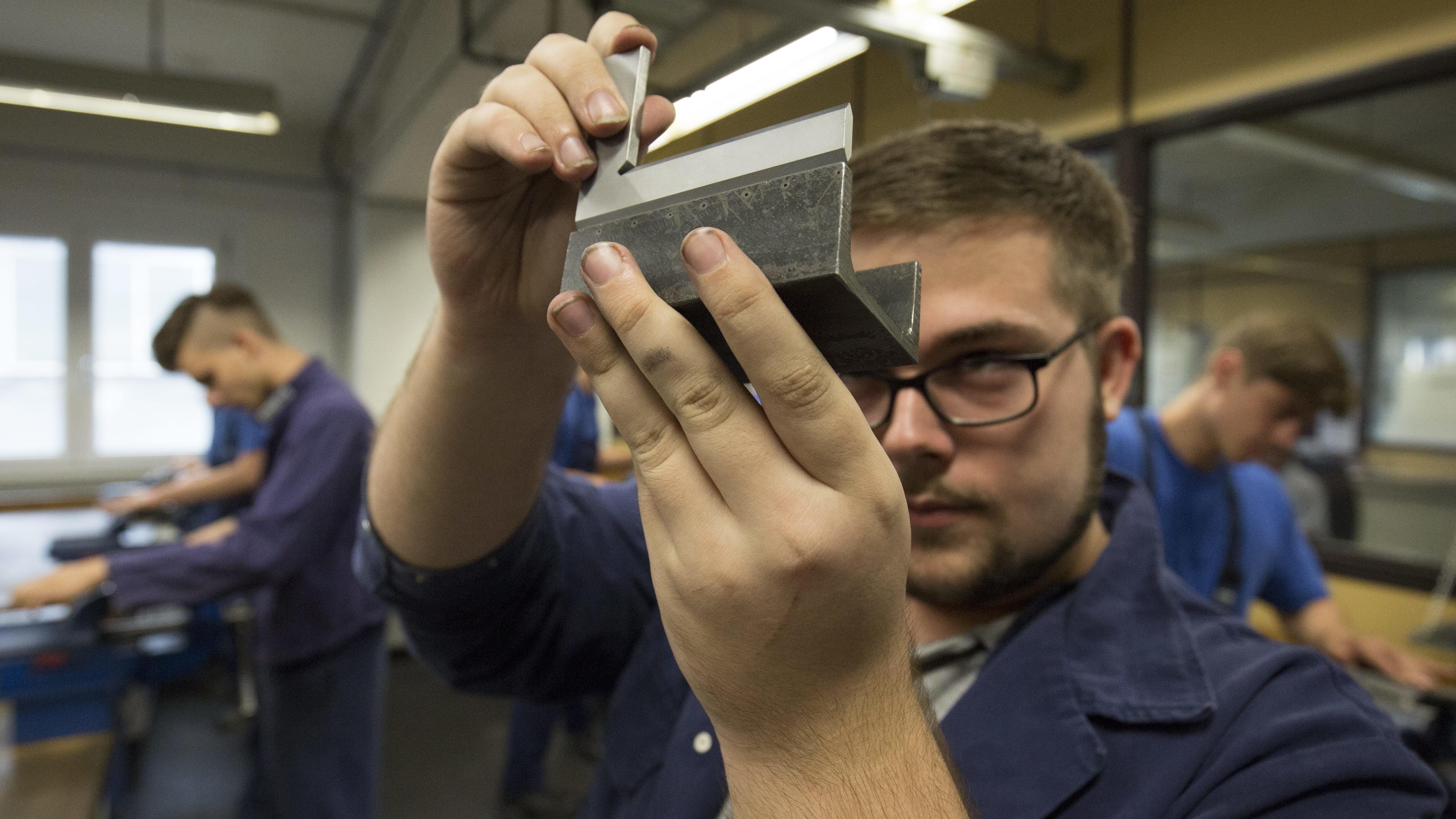 Azubi in einer Schlosserwerkstatt, misst ein Stück U-Stahl.
