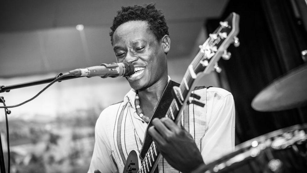Ein Schwarzweiß-Foto des Musikers Ezé Wendtoin aus Burkina Faso mit Gitarre bei einem Auftritt.