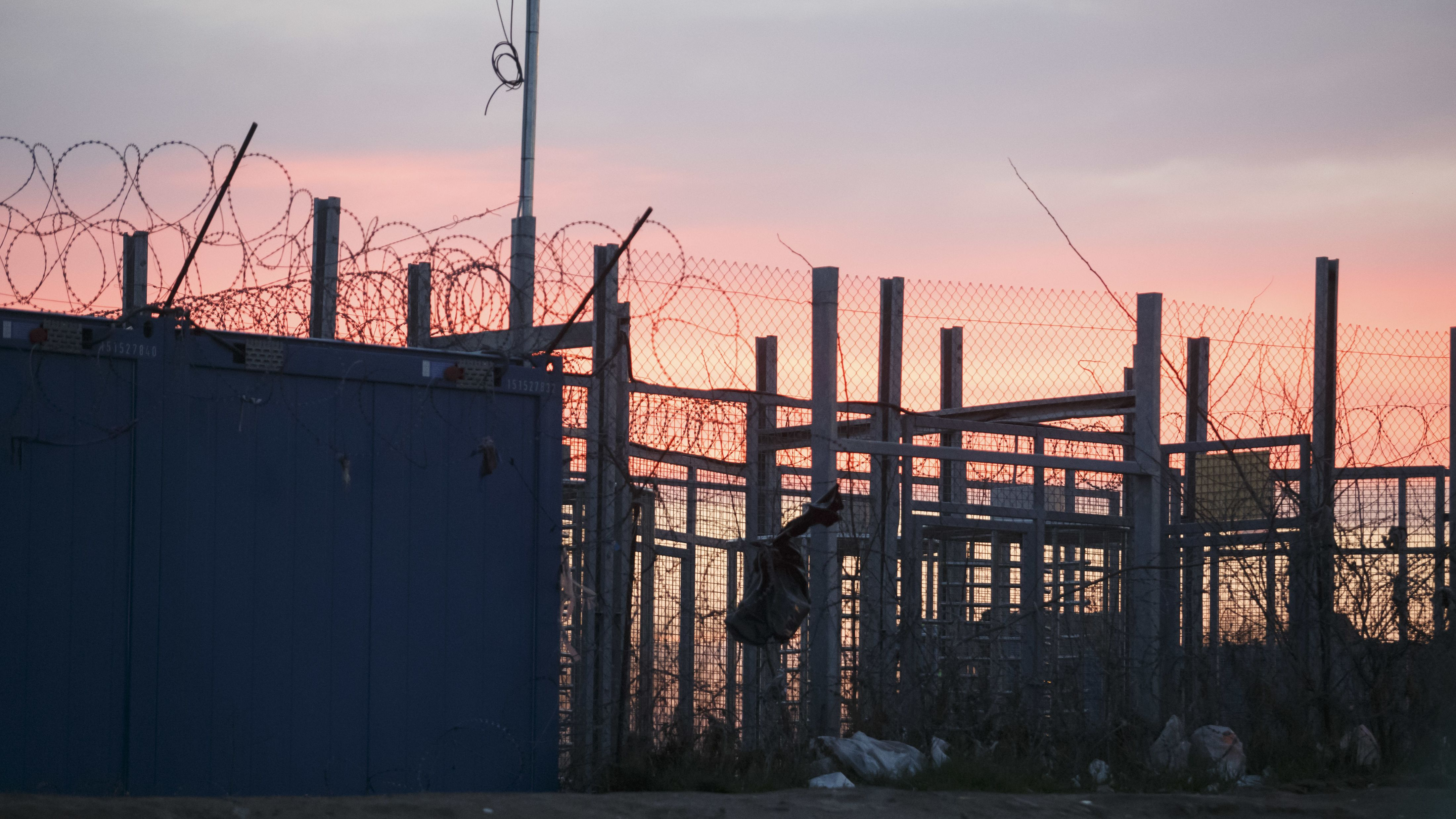 Ein Grenzzaun mit Stacheldraht im Abendlicht