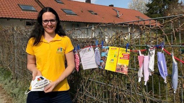 """Petra Fuchs vom gemeinnützigen Verein """"Spielcafé der Generationen"""" neben dem Zaun, an dem die selbstgenähten bunten Masken hängen"""