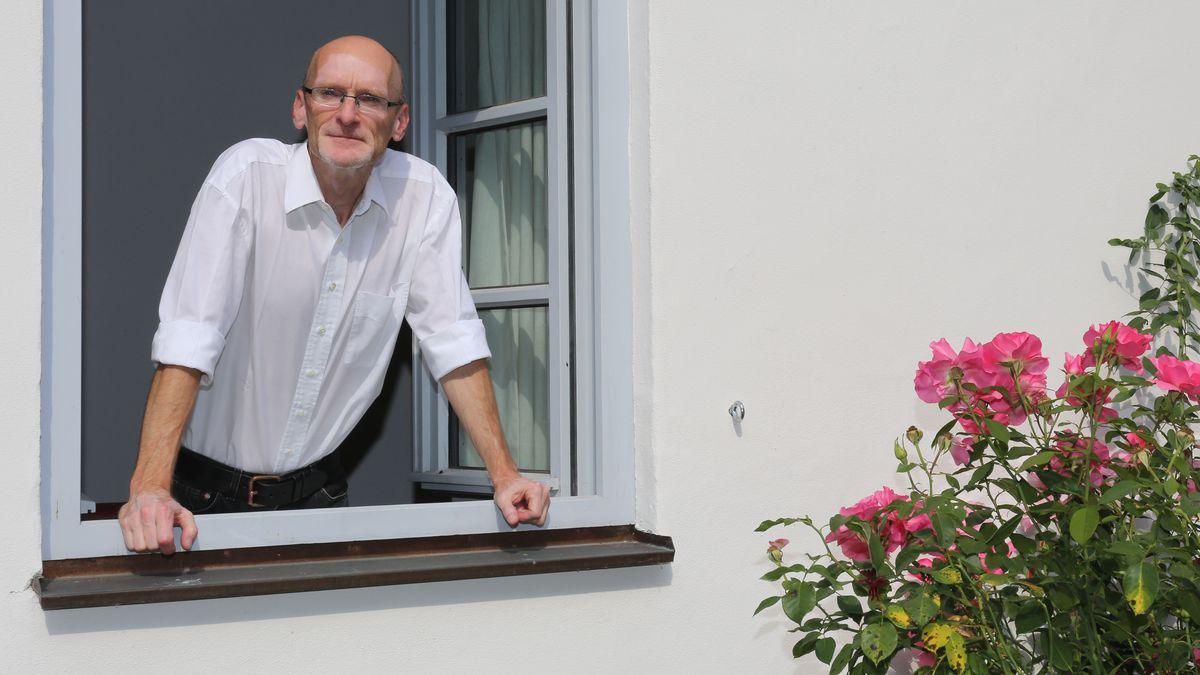Peter Zemla schaut aus einem Fenster.