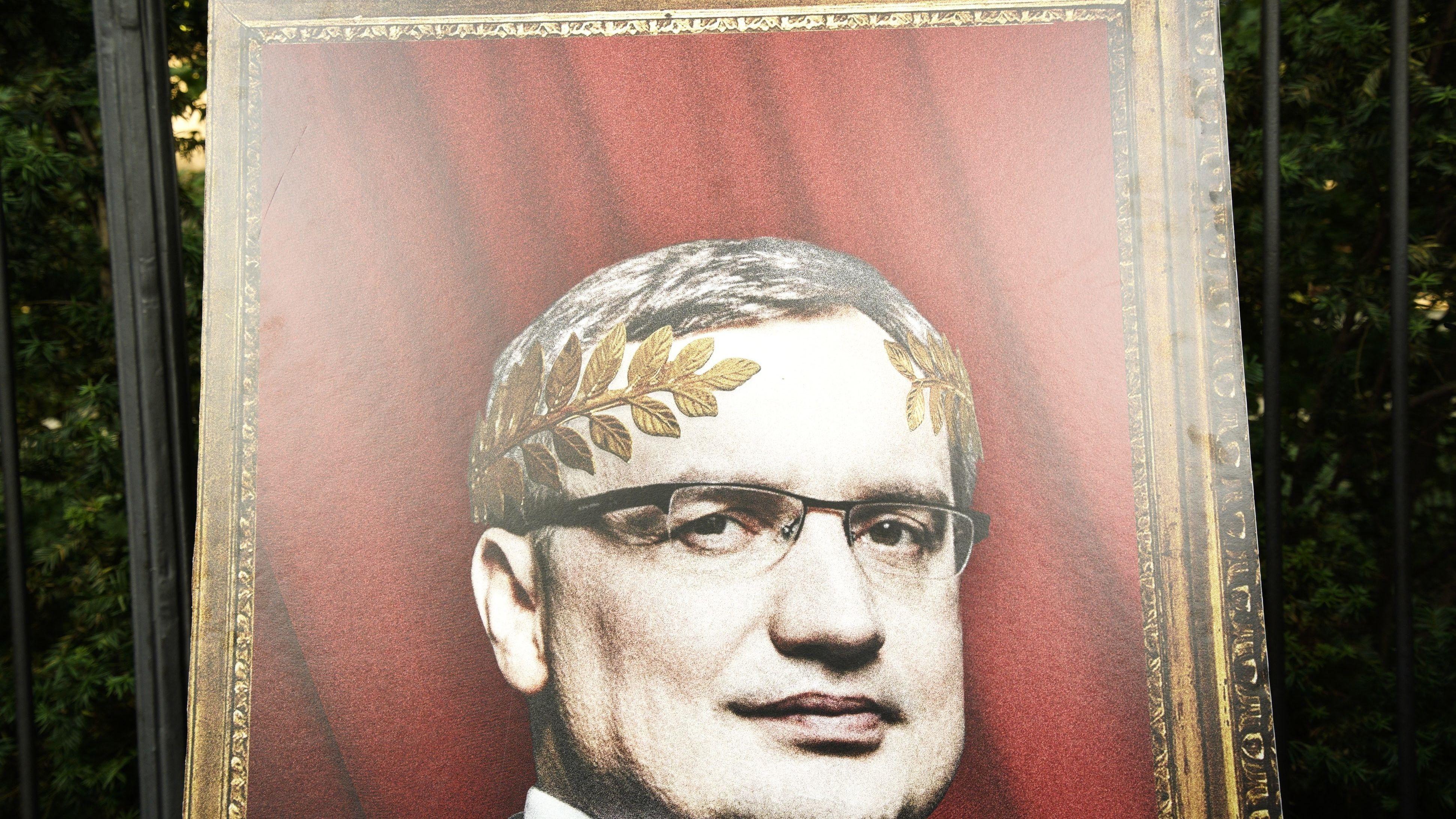 Demonstranten fordern vor dem Amtssitz des polnischen Premierministers den Rücktritt von Justizminister Zbigniew Ziobro und haben ein Foto aufgestellt, bei dem er nach antik-römischem Vorbild einen goldnenen Lorbeerkranz trägt. Er soll in eine Kampagne gegen Richter verwickelt sein.