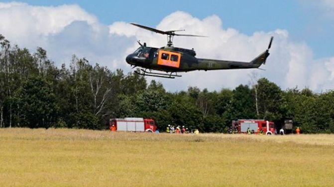 Ein Bundeswehr-Hubschrauber und Feuerwehr-Fahrzeuge am Unglücksort