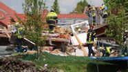 Retter suchen die Trümmer des eingestürzten Hauses in Rettenbach am Auerberg ab. Darunter werden noch ein Kind und ein Mann vermutet.    Bild:News5
