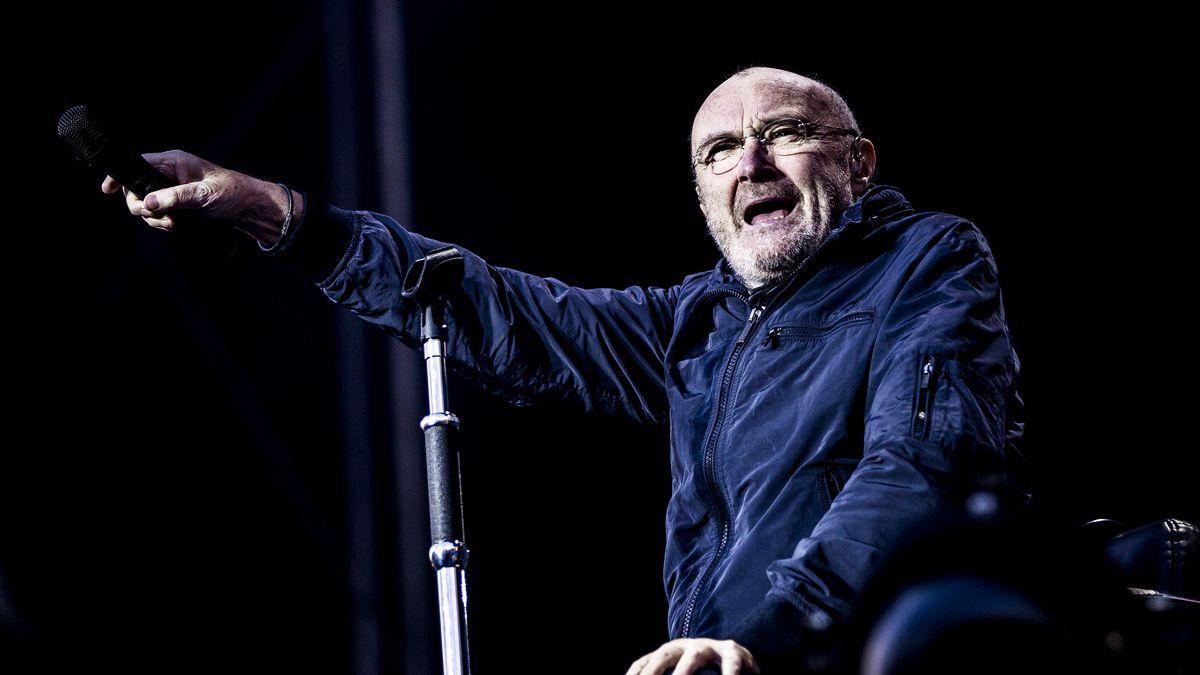 Mann mit blauer Jacke streckt seinen Arm aus. Er hält ein schwarzes Mikro in der Hand.