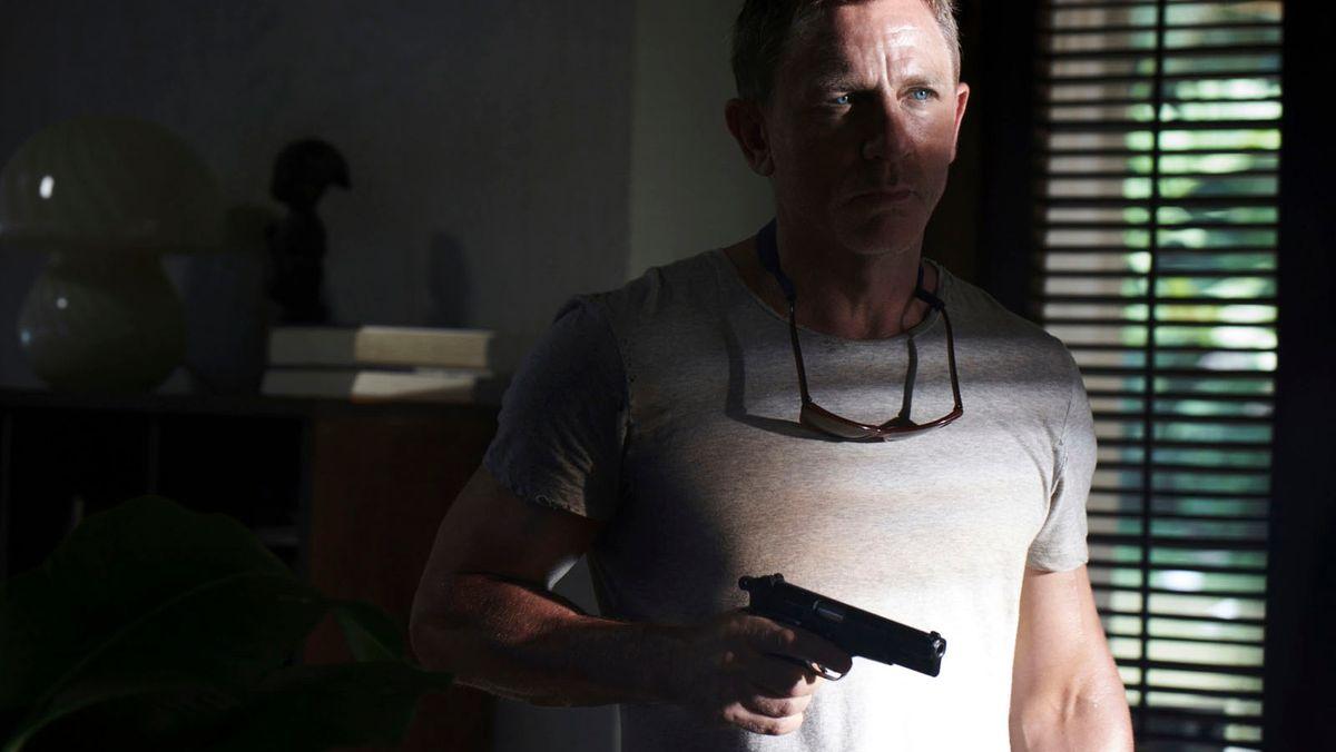 Man sieht Schauspieler Daniel Craig als James Bond, der mit einer gezogenen Waffe im Halbschatten steht.