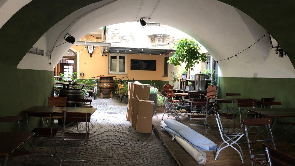 unter Gewölbe in Rosenheim stehen Stühle und Tische eines Biergartens