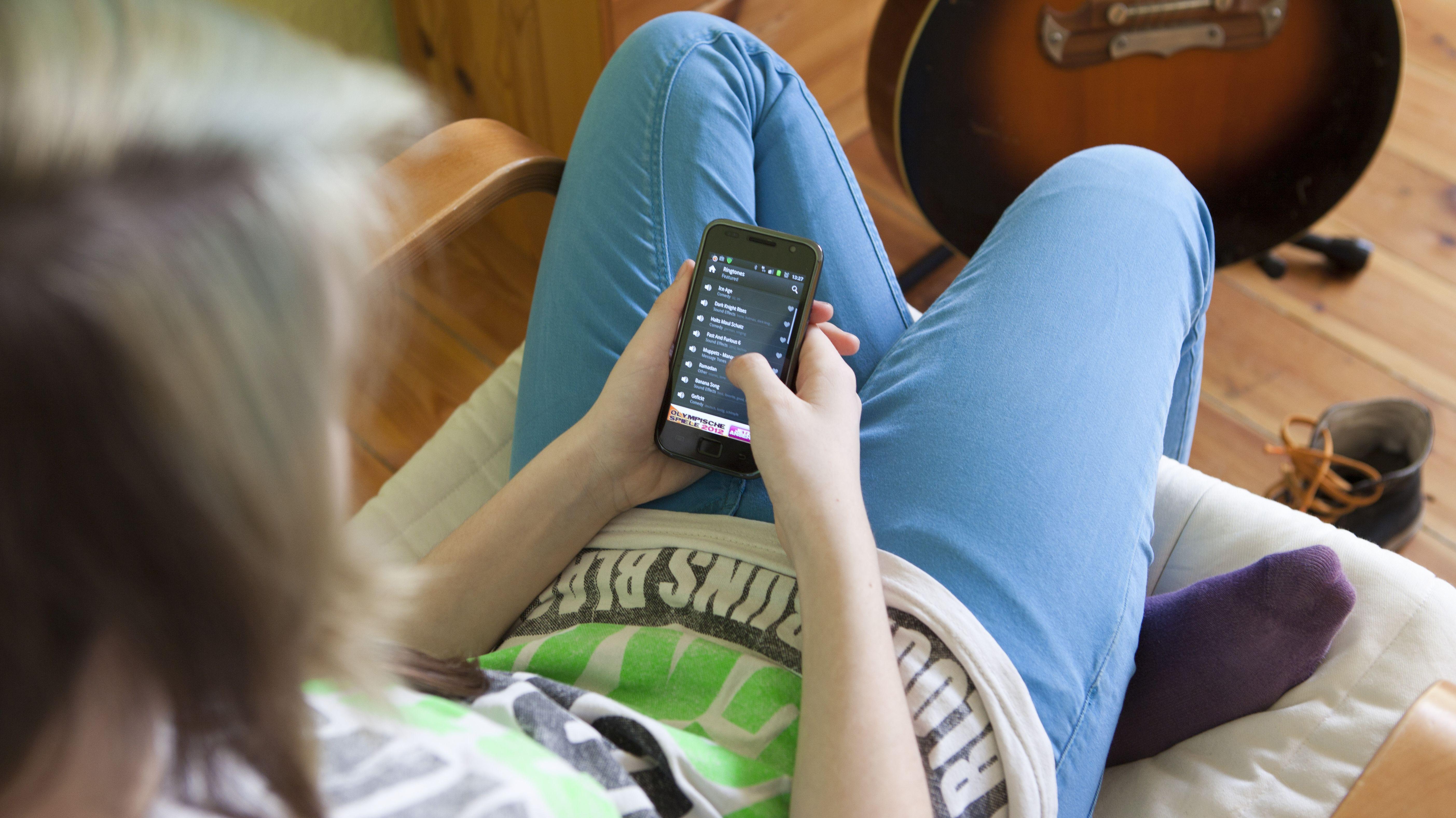 Eine Jugendliche schaut auf ihr Smartphone.