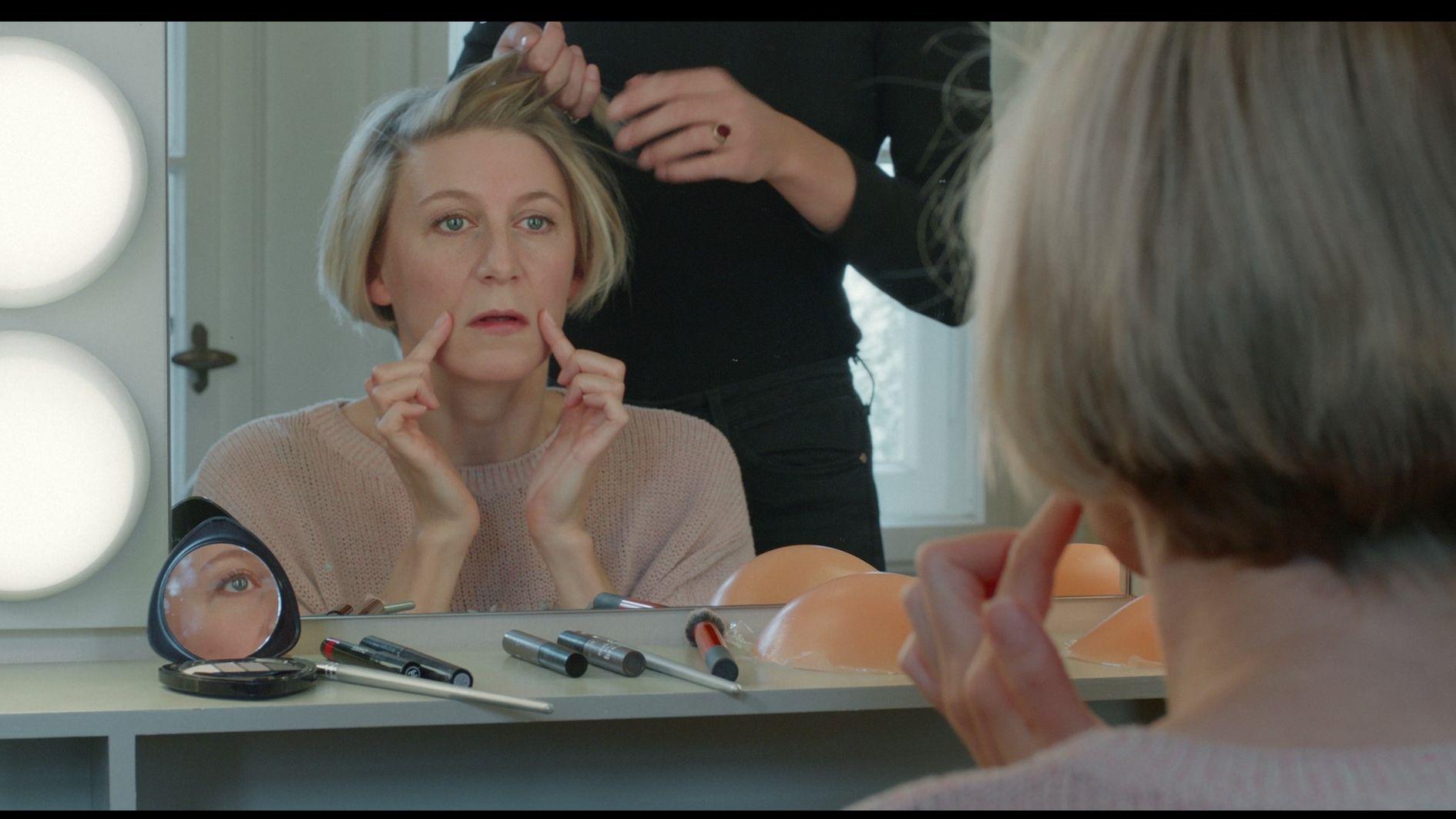 Eine Frau sitzt ratlos angesichtes ihrer Mundfalten vor dem Spiegel und wird geschminkt.