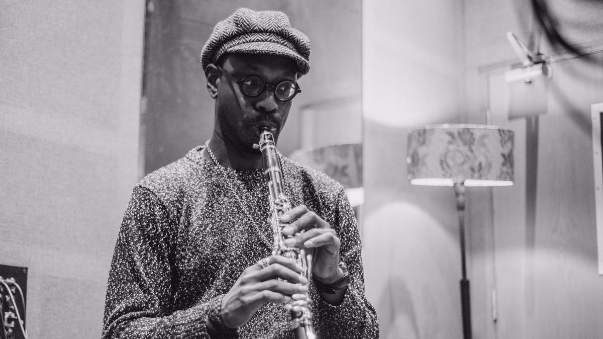 Mit Brille und Mütze  - Shabaka Hutchings spielt Sopransaxofon in einem Studio im Hintergrund ist altmodische Stehlampe zu sehen.