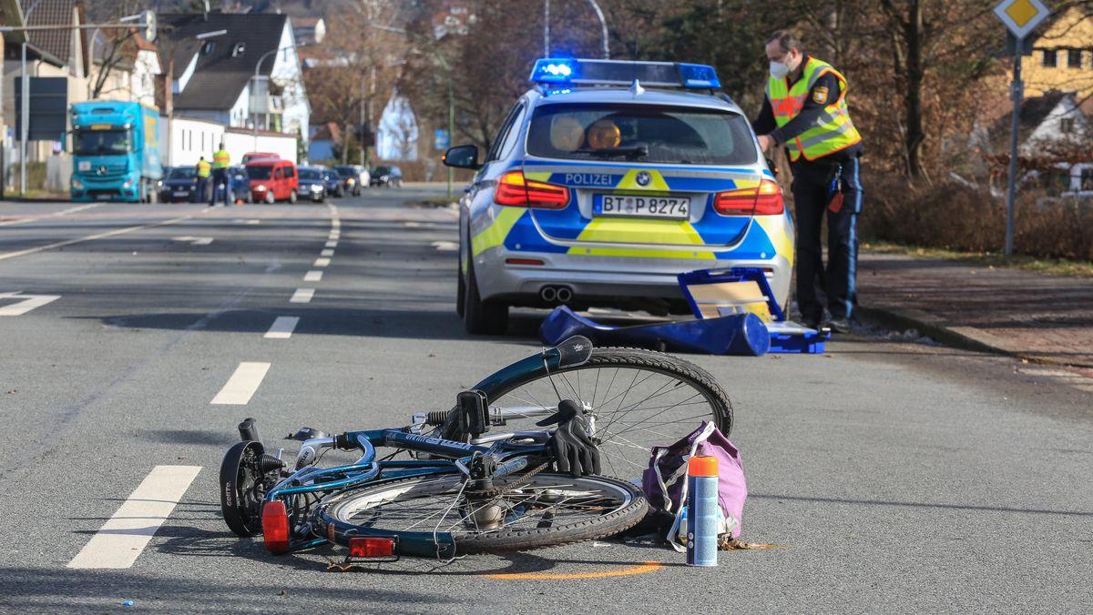In Forchheim liegt ein Fahrrad auf der Straße, das mit einem Auto kollidierte, dahinter ein Polizeiauto.
