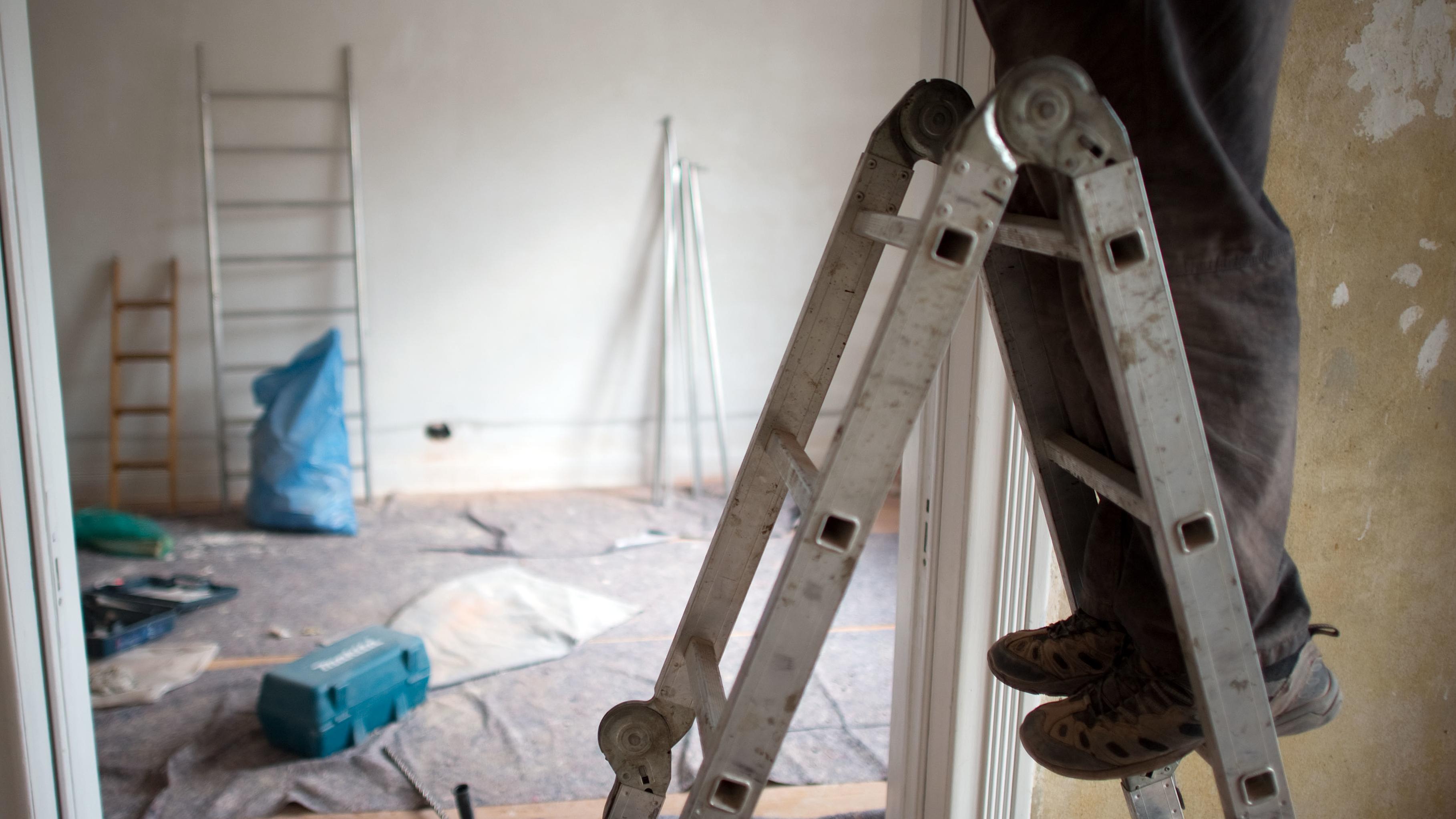 Handwerker auf der Leiter beim Renovieren einer Wohnung