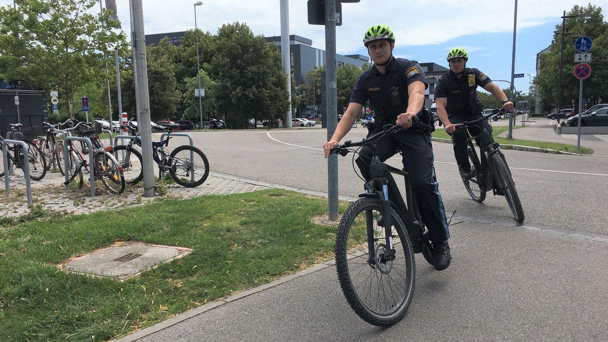Robin Ott und Kevin Buchwald, zwei Polizisten in Ingolstadt, biegen auf ihren Pedelecs in eine Straße ein. Sie tragen blaue Polizei-Uniformen und gelbe Fahrradhelme.