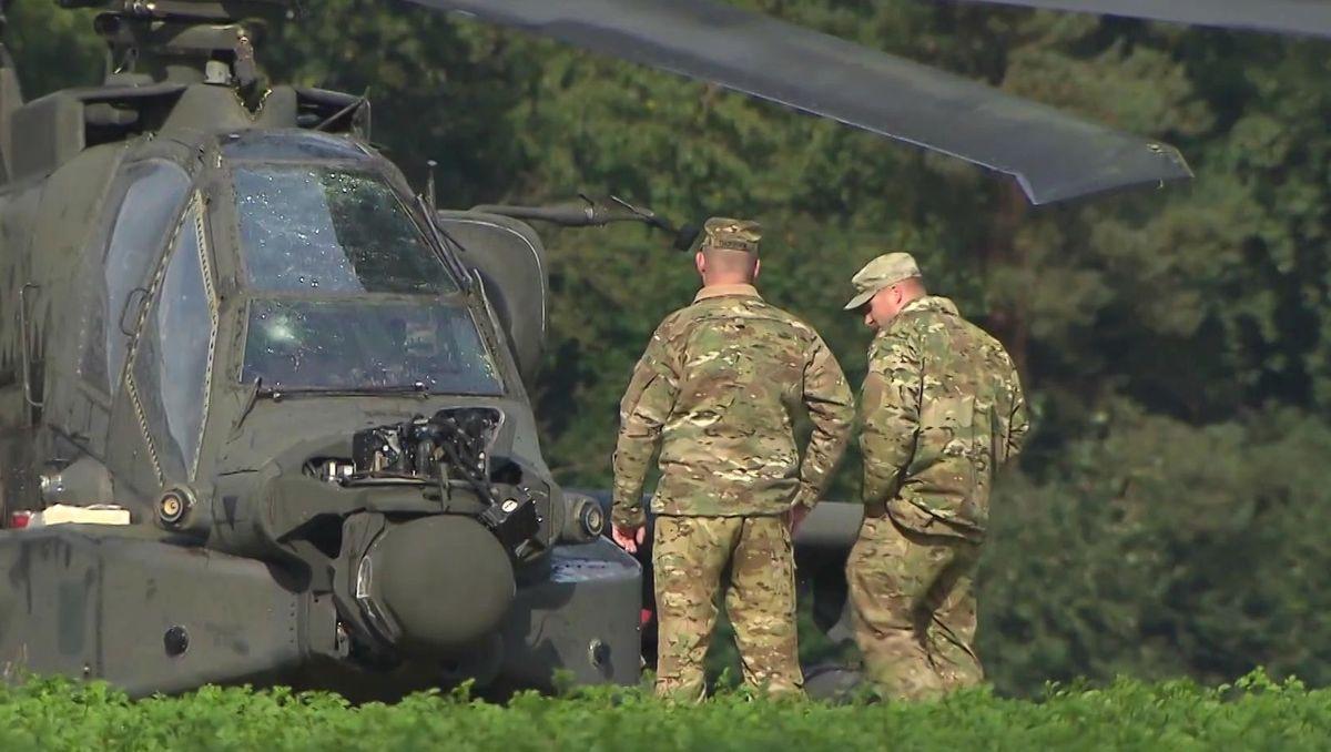 Zwei US-Soldaten neben einem Kampfhubschrauber auf einer Wiese.