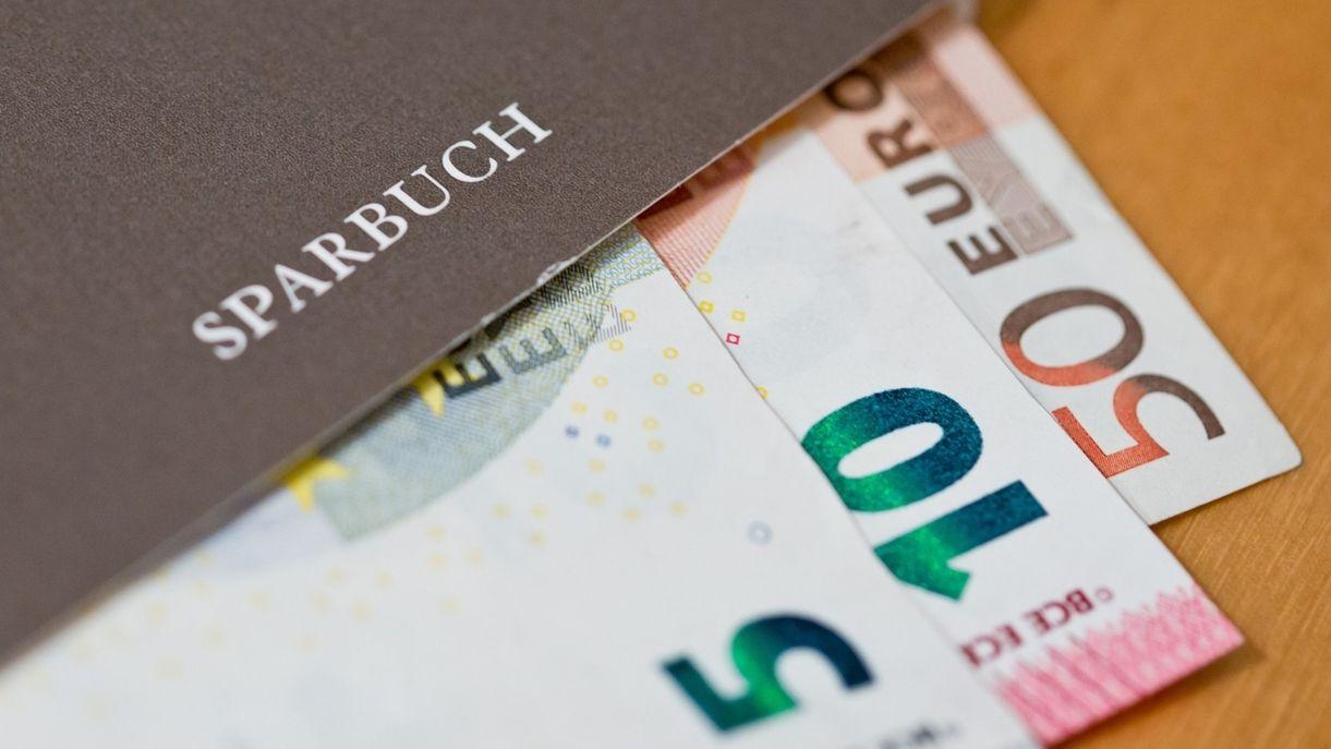 Symbolbild: Sparbuch mit Geldscheinen