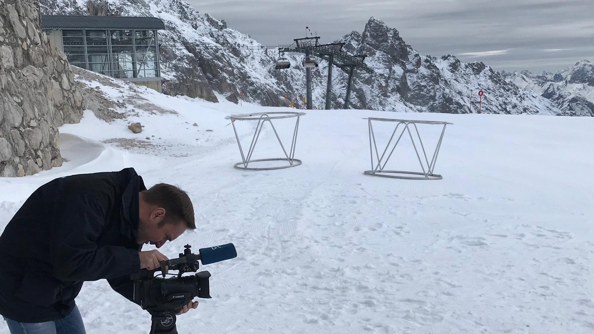 BR-Reporter Martin Breitkopf schaut durch sein Kameraobjektiv auf die Piste auf der Zugspitze.