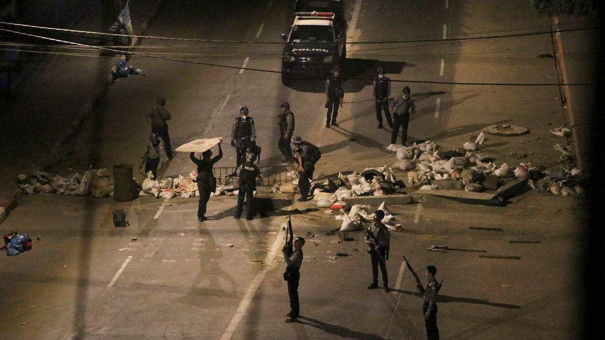 Bewaffnete Polizisten in Yangon entfernen eine Straßenblockade, die von Demonstranten errichtet wurde.
