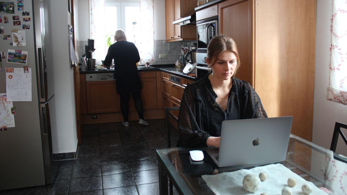Eine junge Frau sitzt an einem Tisch vor einem aufgeklappten Laptop, im Hintergrund eine Person in der Küche.