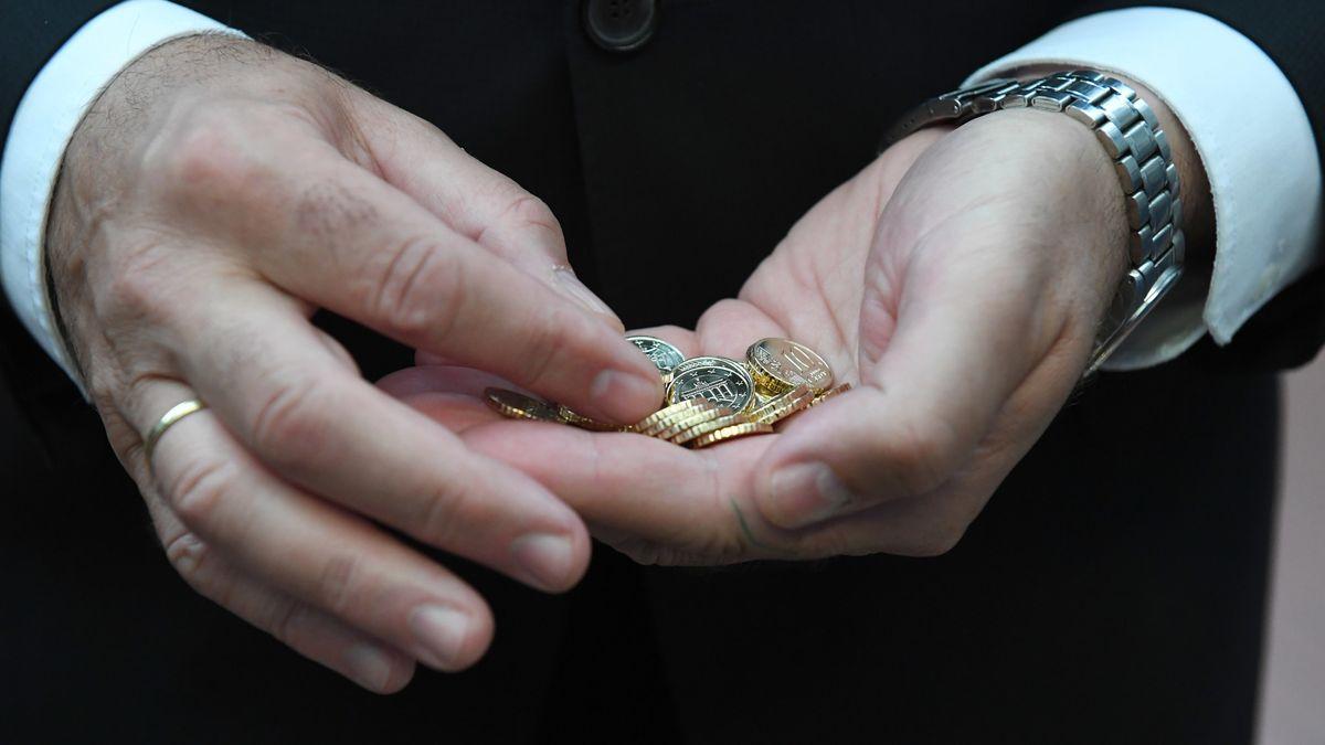 Münzen sind in den Händen des bayerischen Finanzministers Albert Füracker (CSU) im Bayerischen Hauptmünzamt zu sehen. (Archivbild)