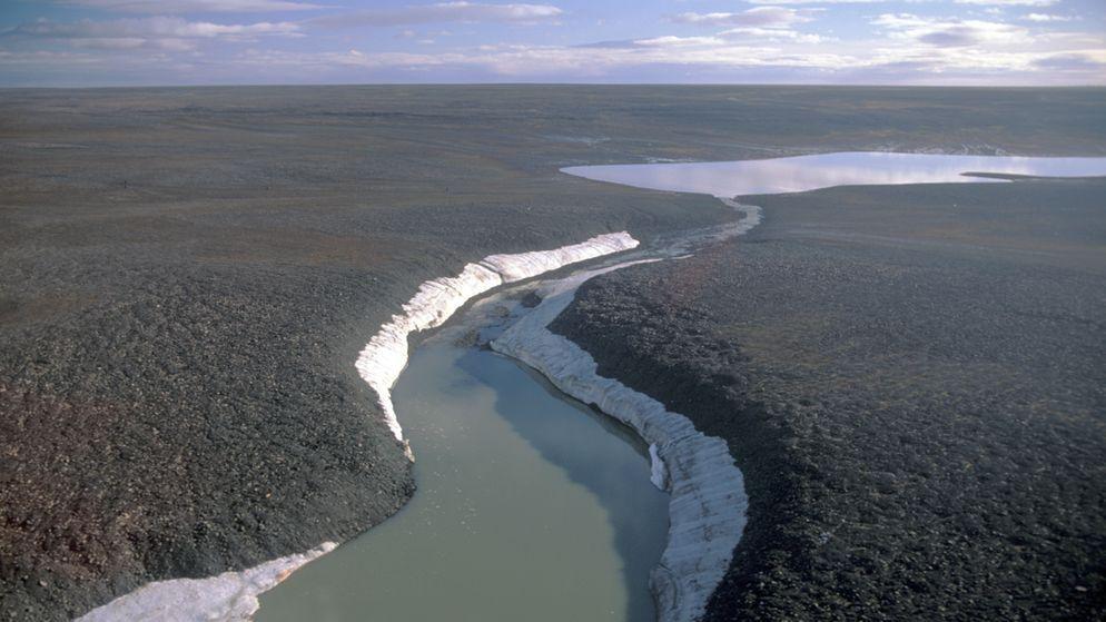Tundra-Landschaft mit einem Schmelzwasser führenden Fluss auf der russischen Bolschewik Insel (Sibirien).
