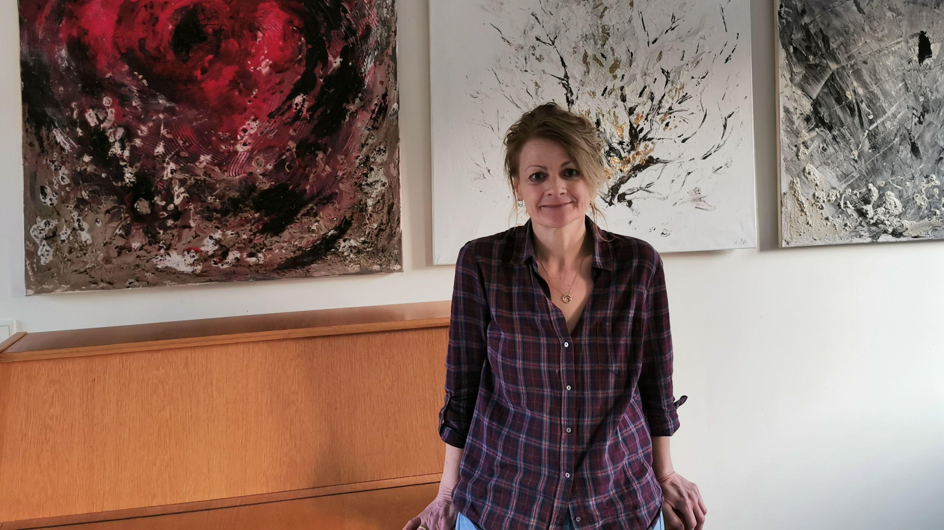 Künstlerin Claudi Wührl vor einigen ihrer Gemälde