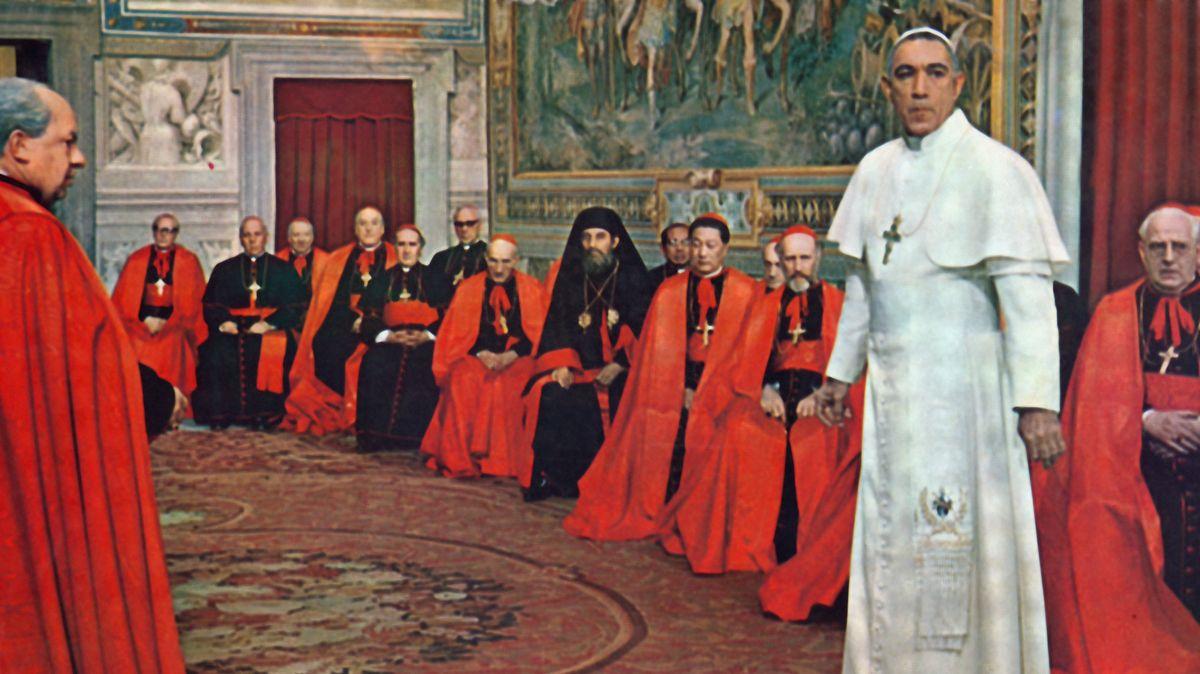 """Szene aus dem Film """"In den Schuhen des Fischers"""": Anthony Quinn steht im weißen Papst-Ornat vor einer Reihe Geistlicher"""