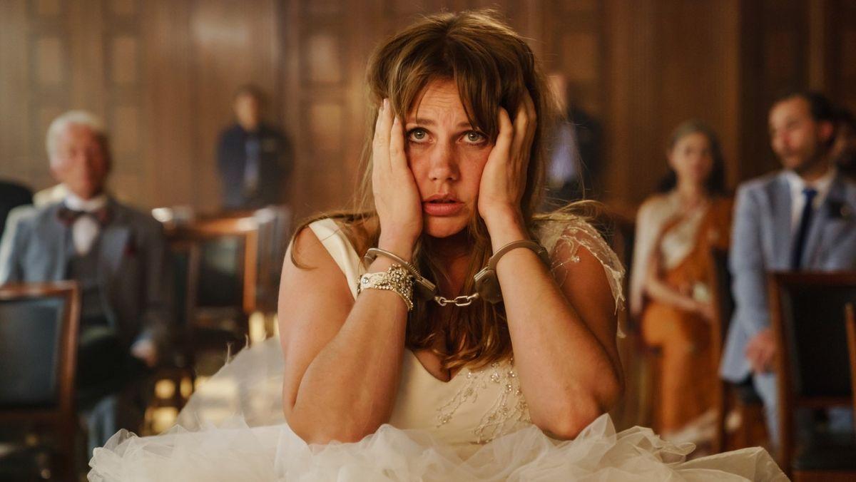 Eine Frau im weißen Brautkleid sitzt mit Handschellen vor einem Richter.