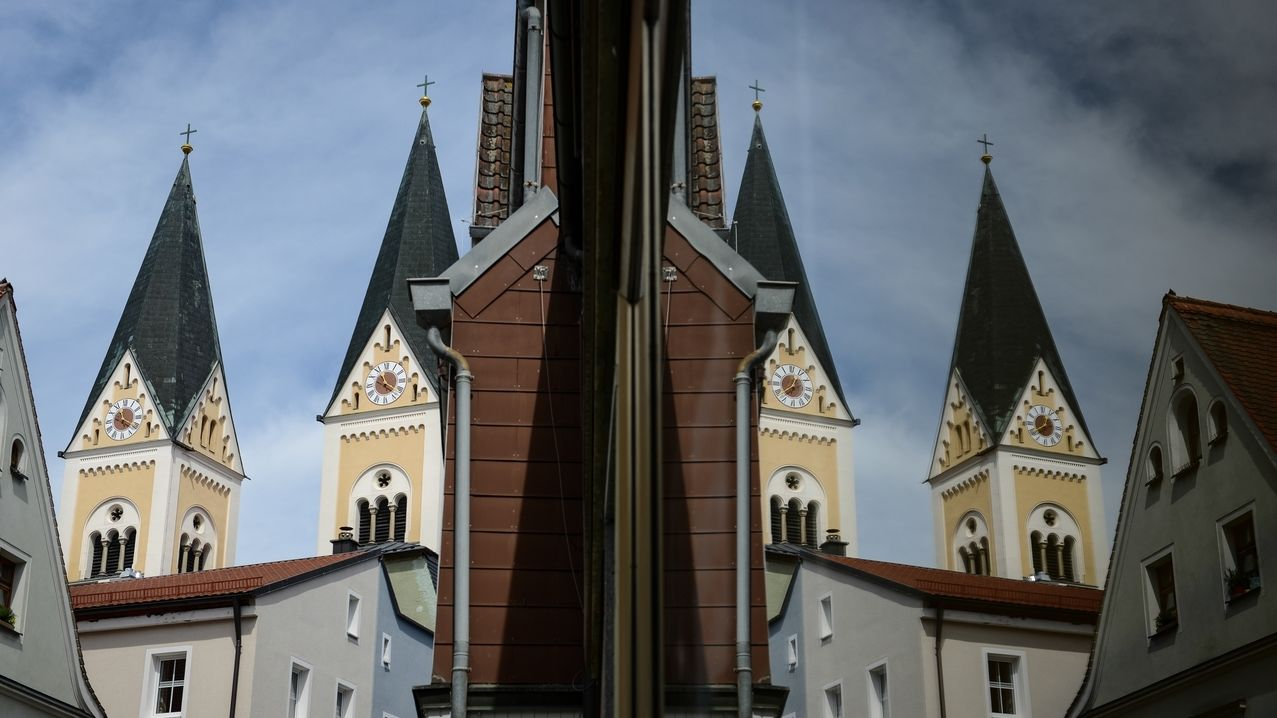 Die beiden Türme der Pfarrkirche St. Josef in Weiden spiegeln sich in einem Schaufenster