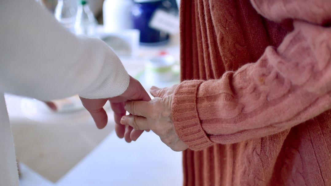 Eine Pflegekraft hält die Hand einer Bewohnerin einer Pflegeeinrichtung.