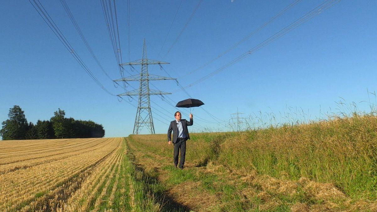 Anwohner Matthias Oberhofer geht mit einem Schirm unter Stromleitungen durch