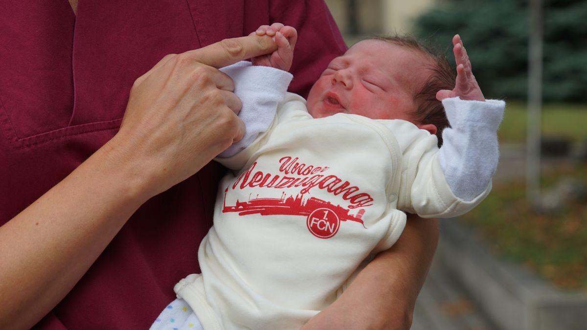 Ein Baby trägt den neuen Fan-Body