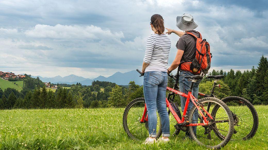 Mann und Frau mit Fahrrädern auf grüner Wiese