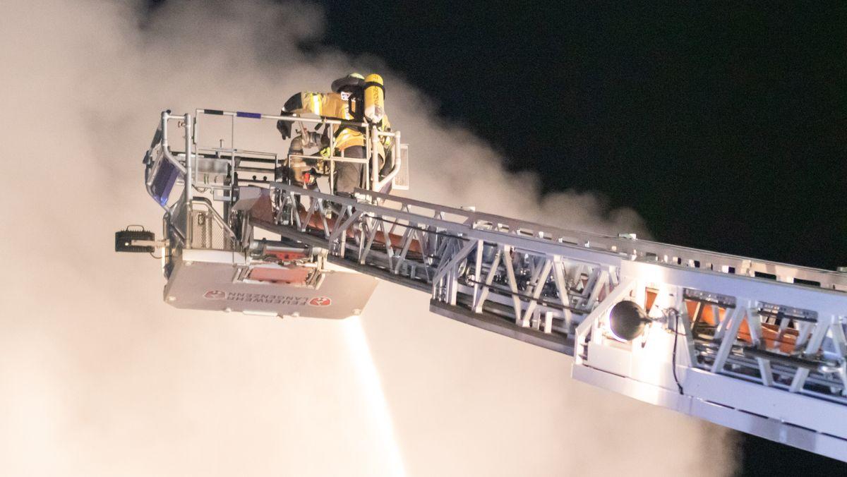 Feuerwehrleute im Korb einer Drehleiter bekämpfen ein brennendes Haus von oben.