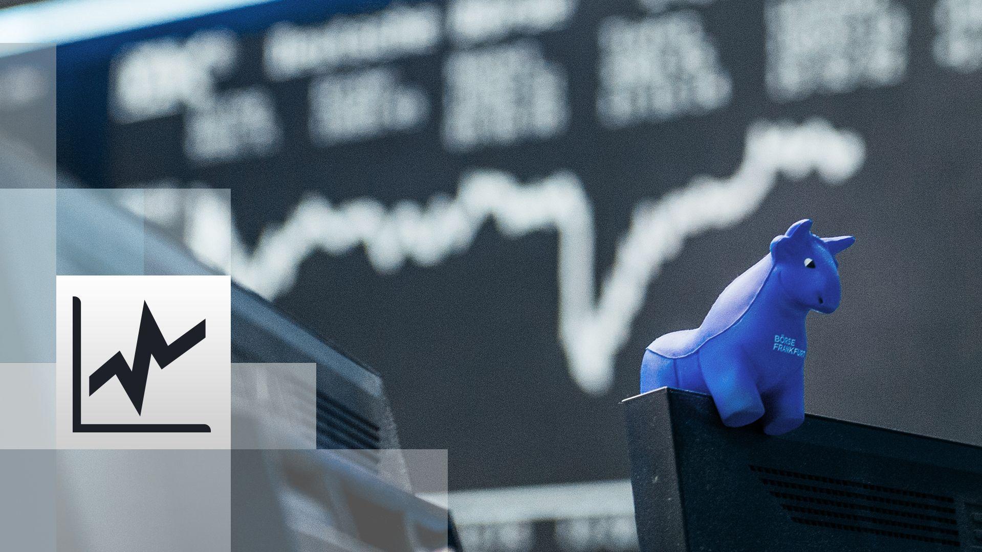 ein blauer Stier aus Gummi sitzt auf der oberen Kante eines Bildschirmes, im Hintergrund die Kurstafel der Börs