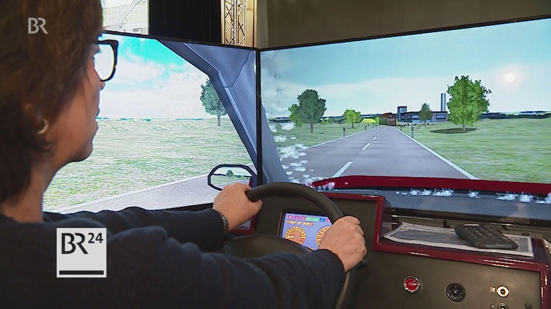 Eine Frau fährt in einem Fahrsimulator.