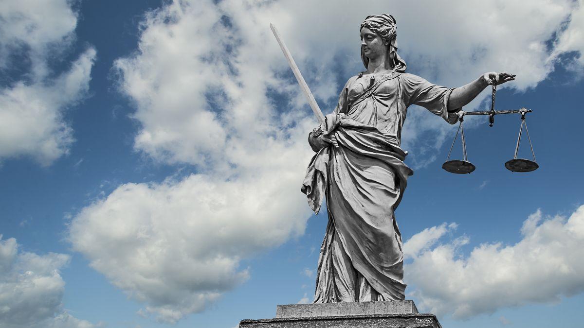 Statue einer Justizia mit Waage und Schwert vor einem Wolkenhimmel (Symbolbild)