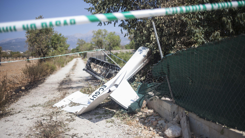 Wrackteile liegen nach der Kollision eines Ultraleichtflugzeugs mit einem Hubschrauber in der Nähe der Absturzstelle hinter Absperrband.