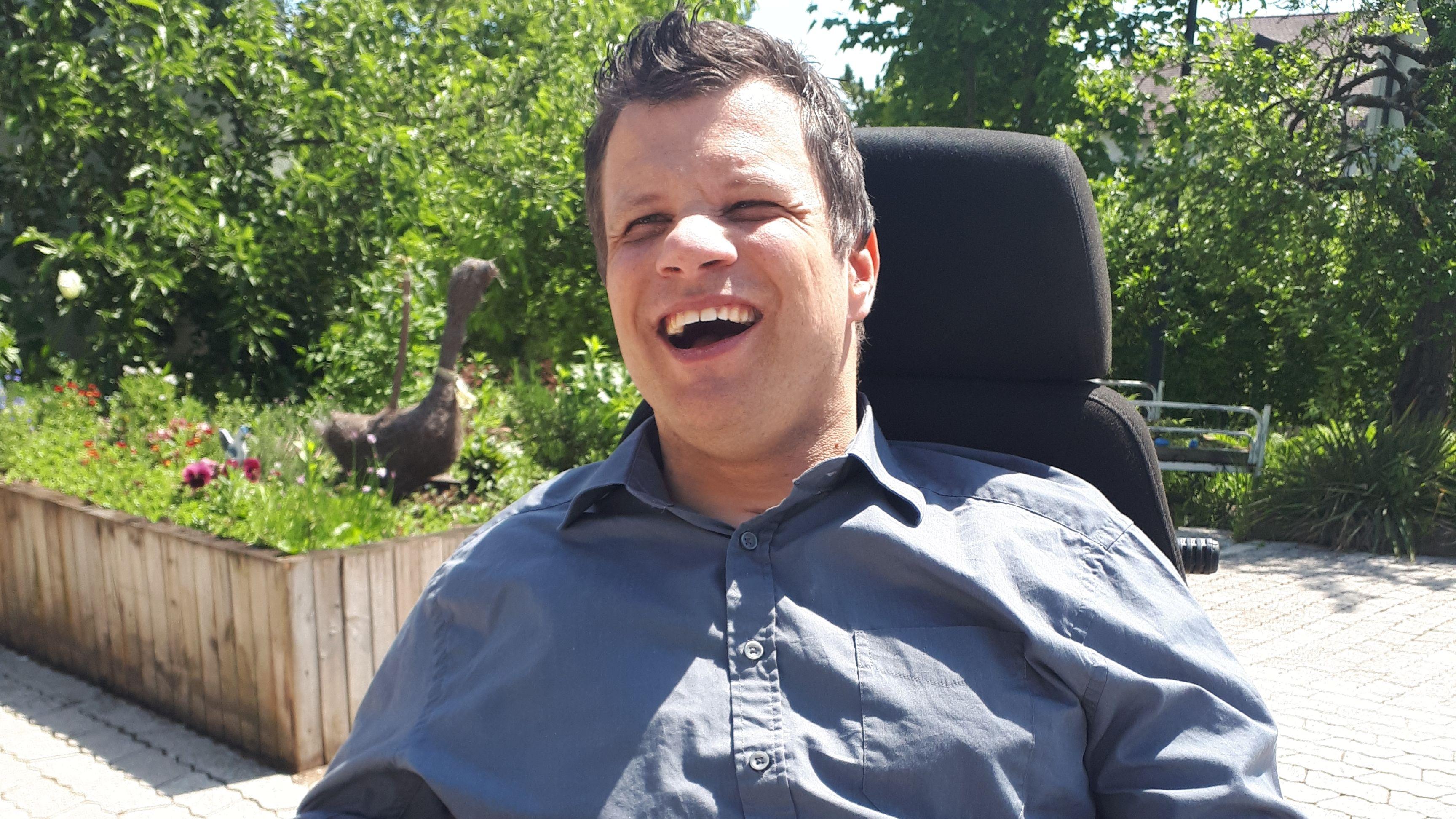 Ein Mann im Rollstuhl lacht. Der Grund: seine erste Teilnahme an einer EU-Wahl.