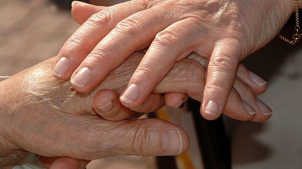 Eine Hand hält eine zweite.